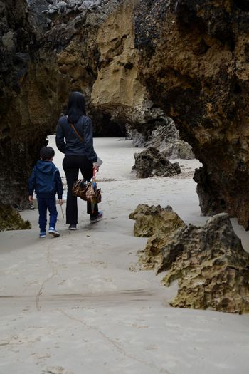 Mother and son walking through natural arch at beach