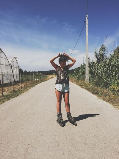 Full length of woman in roller skate standing on road against sky during sunny day