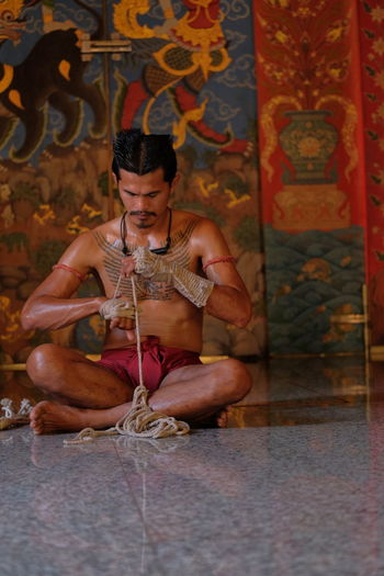 Full length of man working with rope while sitting in temple