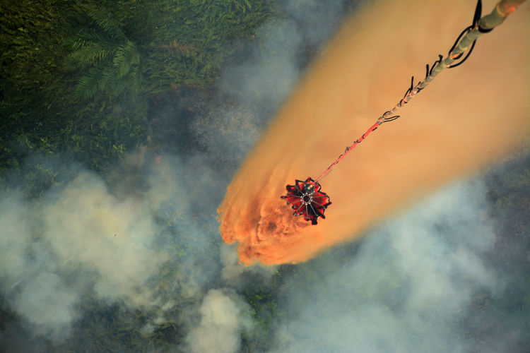 High angle view of retardant falling from container over forest fire