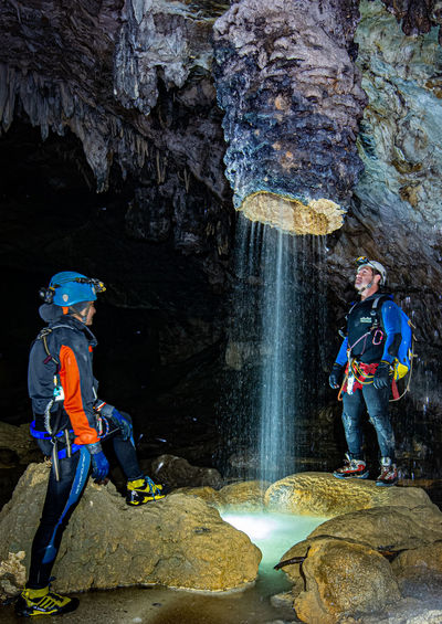 Friends standing on rocks in cave