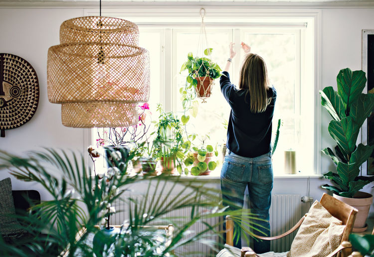Rear view of woman standing by potted plants at home