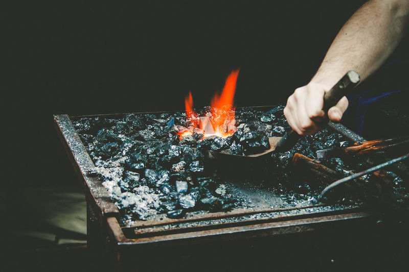 Cropped Hand Of Man Preparing Barbecue At Night