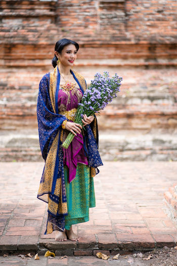 Full length of holding bouquet while standing outdoors