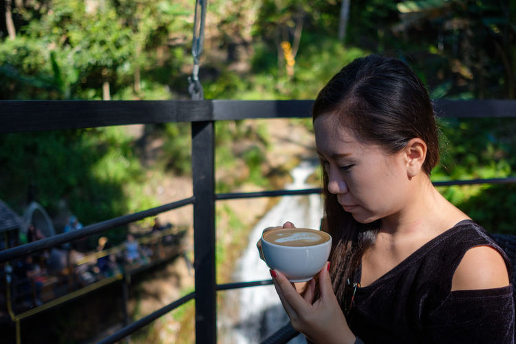 Close-Up Of Woman Holding Coffee Cup Outdoors