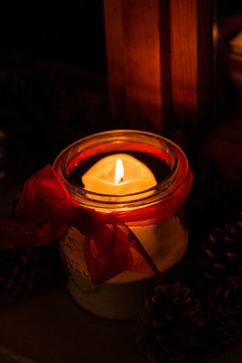 Burning candle in a glass and fir cones in the dark Burning Fire Candle Flame Fire - Natural Phenomenon Illuminated Heat - Temperature Indoors  No People Glowing Tea Light Nature Close-up Oil Lamp Decoration Flower Dark Container Lighting Equipment Flowering Plant Electric Lamp
