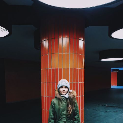 Girl standing by pillar at parking lot