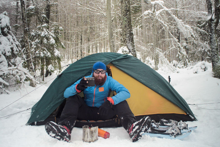 winter camping on snow, hiker sitting in a tent having a cup of hot beverage Camping Cooking Expedition Exploring Freezing Hiking Man Stove Travel Trekking Winter Adventure Clothing Cold Cold Temperature Day Front View Full Length Holiday Land Leisure Activity Male Nature Nutrition One Person Outdoors People person Shelter Sitting Snow Snowshoeing Snowshoes Survival Tent Trail Tree Trip Vacations Warm Clothing Winter