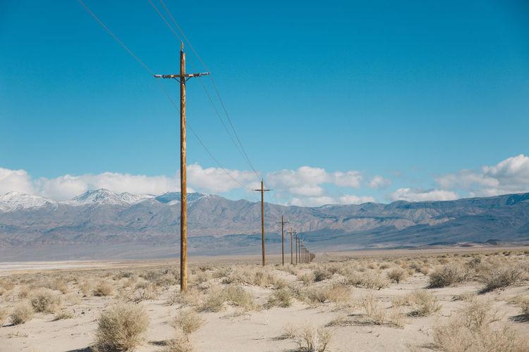 Electricity pylon on landscape against blue sky