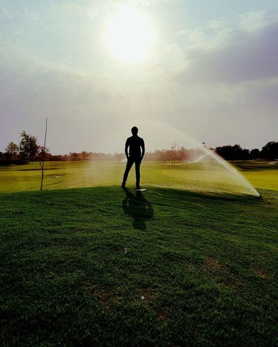Man standing by sprinklers on grassy field against sky