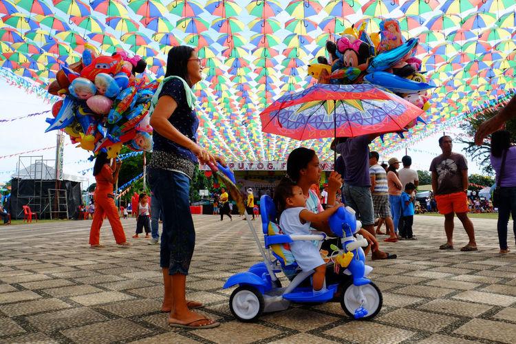 People sitting on multi colored umbrellas against sky
