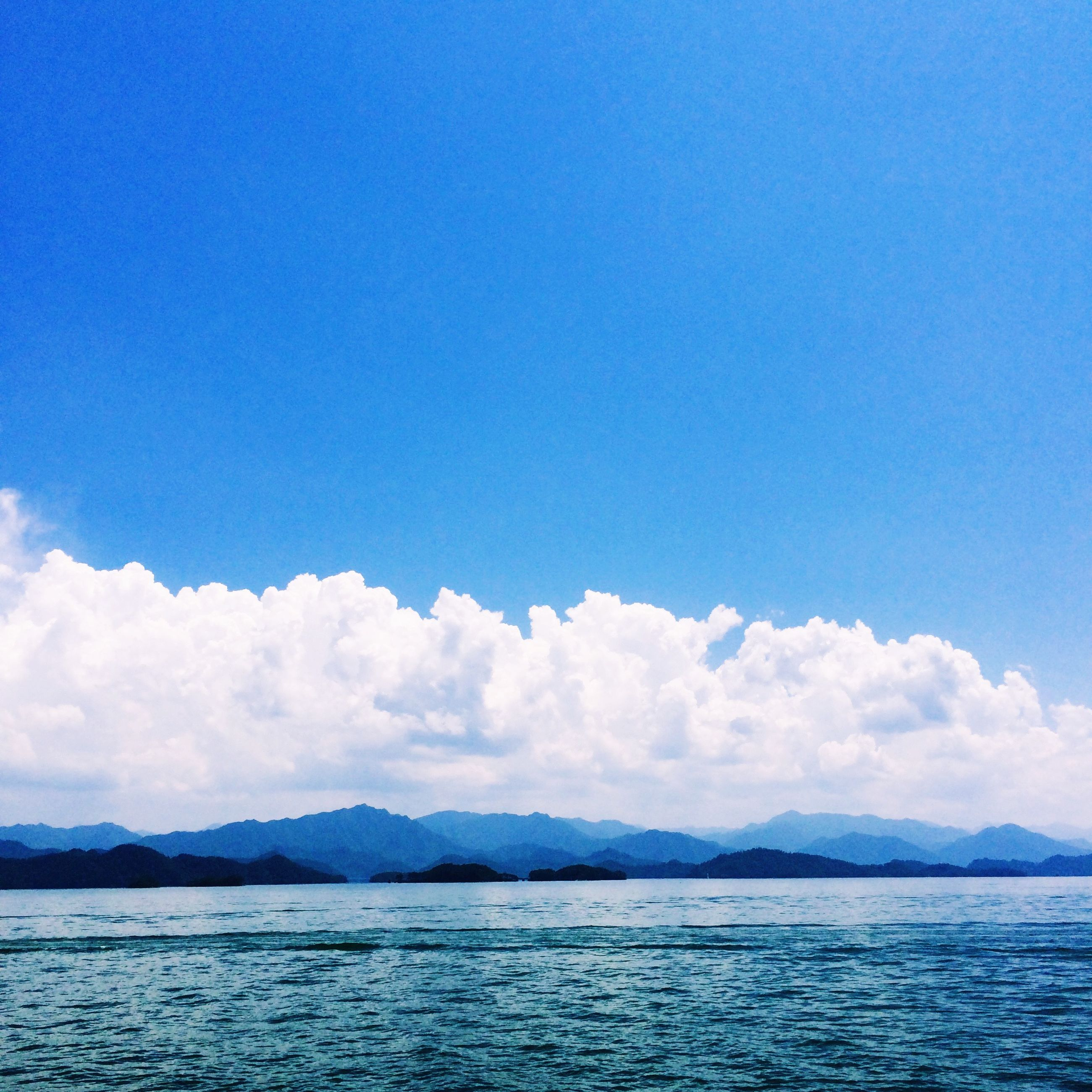 water, waterfront, mountain, tranquil scene, scenics, tranquility, mountain range, beauty in nature, sky, sea, blue, nature, rippled, idyllic, lake, cloud, copy space, cloud - sky, calm, outdoors