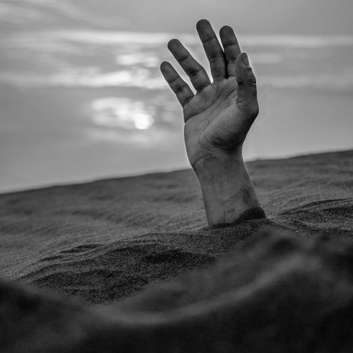 Close-Up Of Persons Hand Buried Under Sand