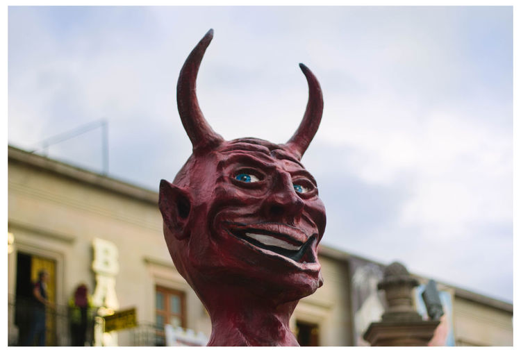 Low angle view of devil statue against sky