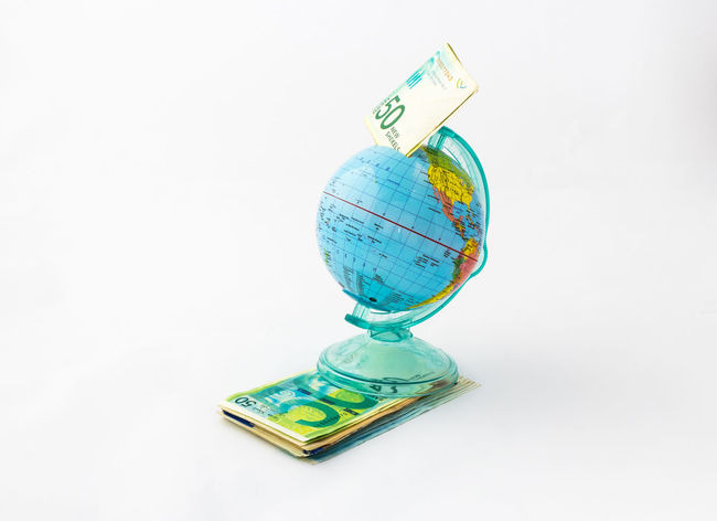 A money box made in the shape of a planet Earth globe with an inserted banknote worth fifty Israeli shekels in the money slot at the top, stands on a stack of Israeli banknotes of different value, isolated on a white background. Business Currency Earning Earth Isolated Art Bank Banknote Buy Cash Coin Coins Design Exchange Finance Globe Israel Money Pay Planet Shekel Stock Studio Shot Wealth White Background