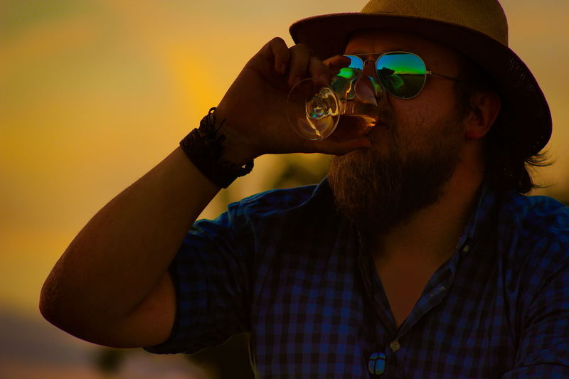 """Rule 1 of life. Do what makes YOU happy."" – Unknown Beard Beardy Casual Clothing Drink Drinking Exceptional Photographs EyeEm Best Shots - People + Portrait Eyeglasses  Hat Headshot Leisure Activity Lifestyles Light And Shadow Mid Adult Sunset People And Places Uniqueness"