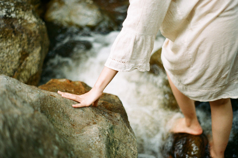 Low section of woman on rock by stream