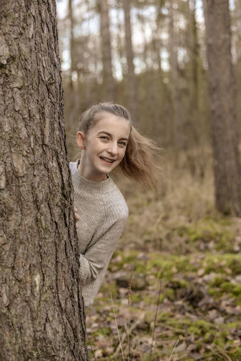 Portrait of smiling teenage girl standing behind tree in forest