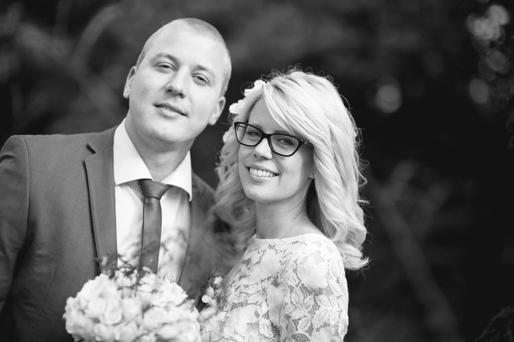 Portrait of smiling bridal couple standing at park