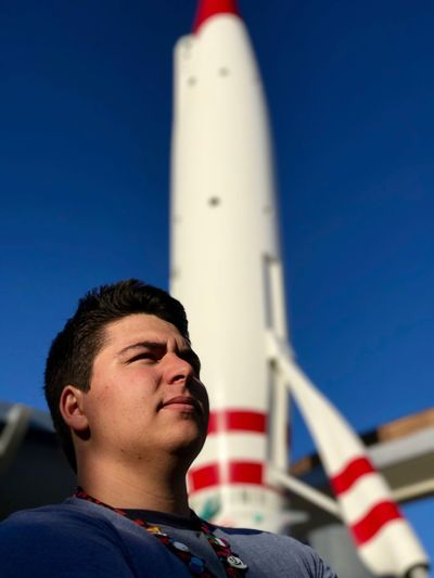 Close-up of man standing against rocket