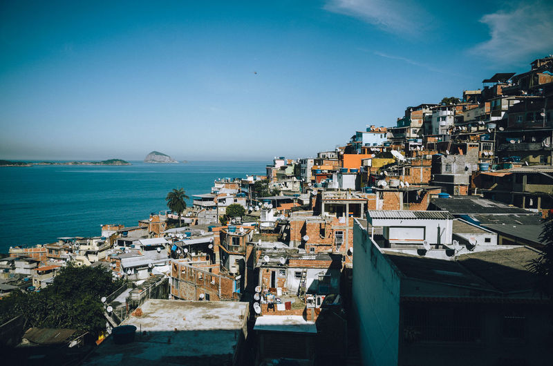 High angle view of brazilian slum by sea against clear sky