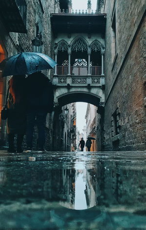 Barcelona Stories From The City Waterdrops Rainy Days Umbrella Eyemphotography Eyem Best Shots Light And Shadow Rainy Days Reflection Water Men Reflection Architecture Built Structure Rainfall Rain Puddle RainDrop Historic Building Arch Bridge Rainy Season