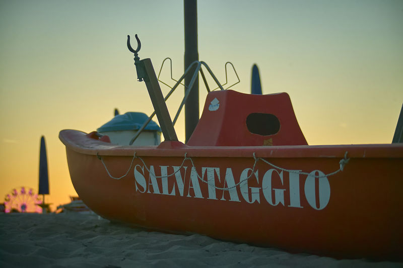 Beach Clear Sky Communication Day Focus On Foreground Land Lifeboat Station Mode Of Transportation Moored Nature Nautical Vessel No People Outdoors Sea Sky Sunset Text Transportation Water Western Script
