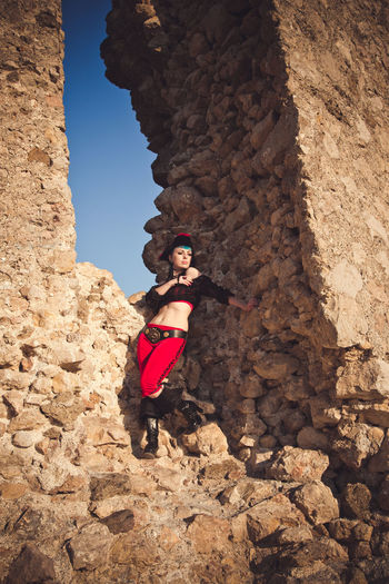 Low angle view of woman standing on rock