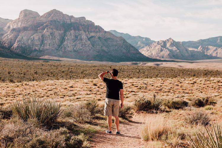 Rear view full length of man standing at desert against sky
