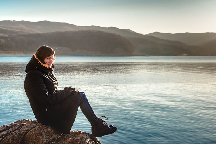 Young woman looking at lake against mountain range