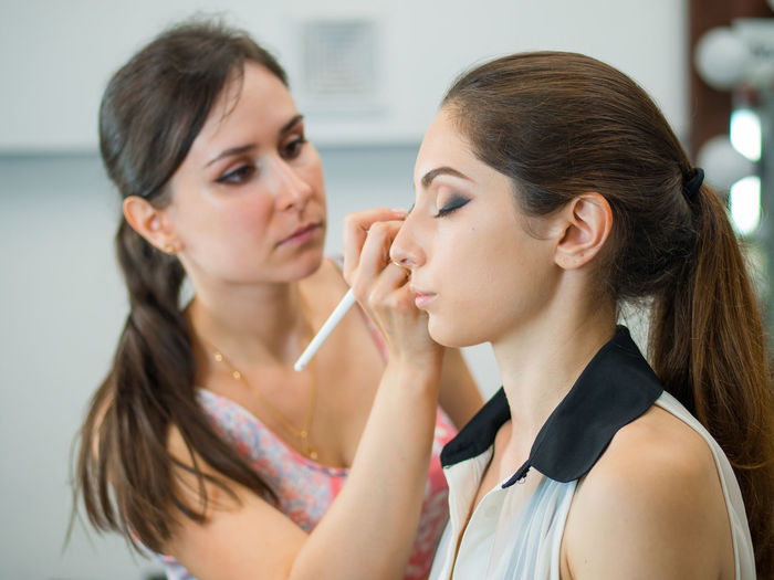 Artist Applying Make-Up On Young Woman In Beauty Spa
