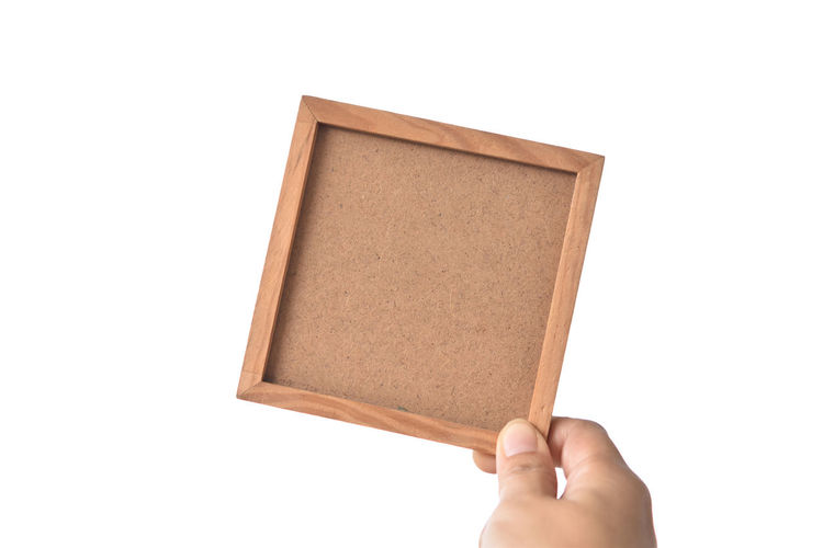 Low section of person holding paper against white background