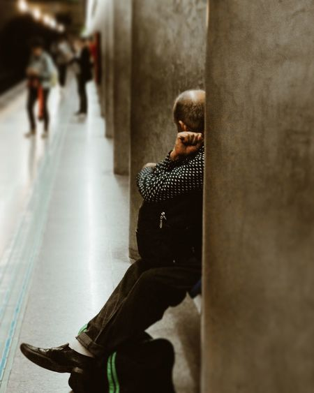 Side view of a man sitting against wall
