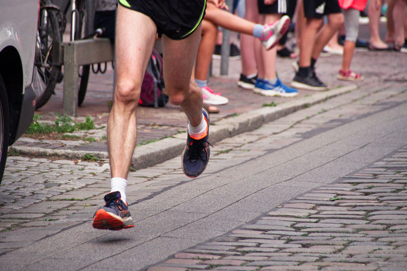 Low Section Of Athlete Running Marathon On Street With People In Background