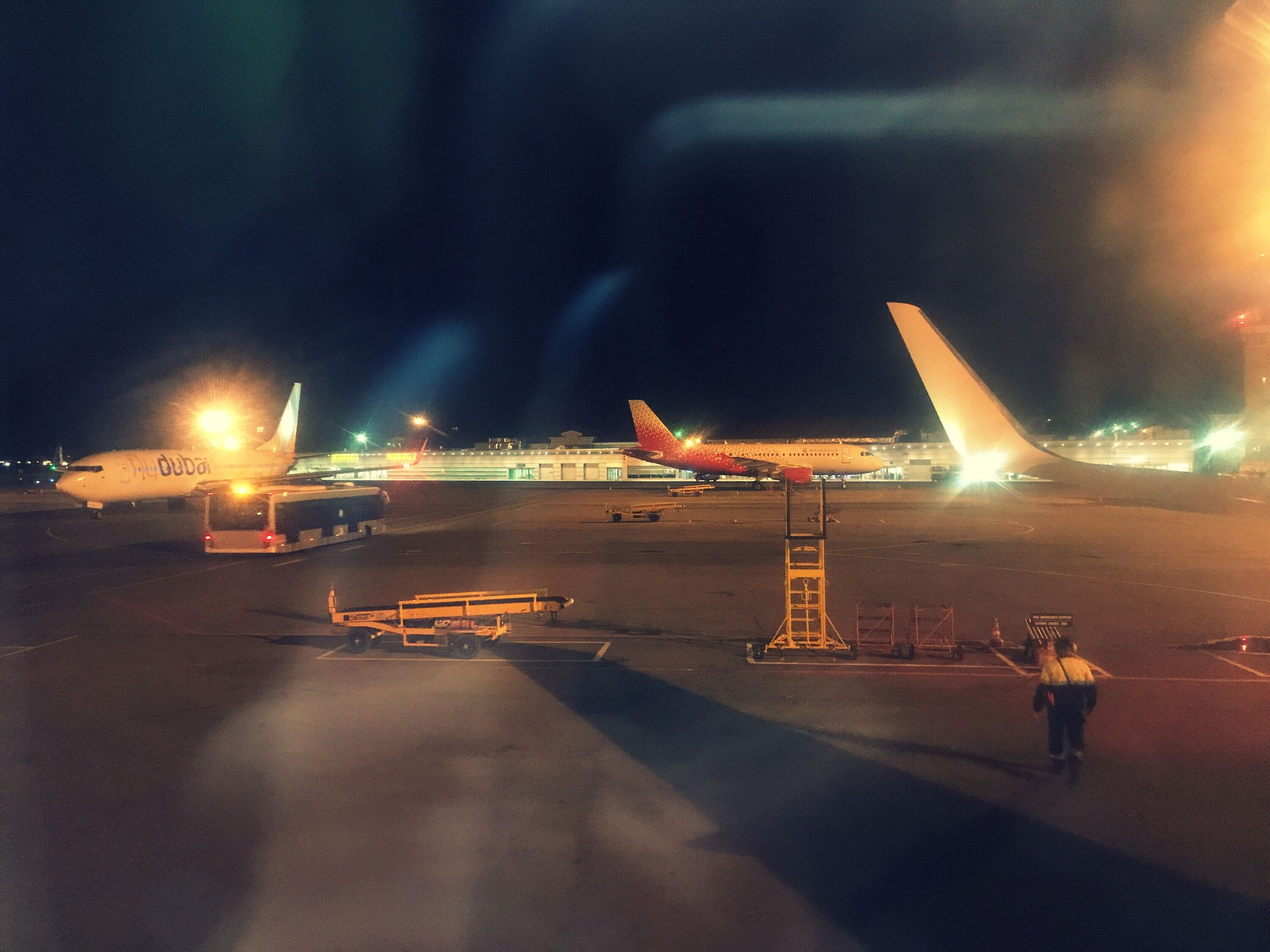 illuminated, night, airplane, transportation, air vehicle, mode of transport, airport, sky, airport runway, outdoors, built structure, no people, light beam, runway, water, architecture, building exterior, nature
