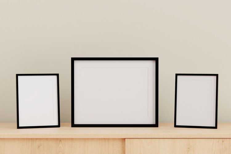 Close-Up Of Blank Picture Frames On Table Against Gray Wall
