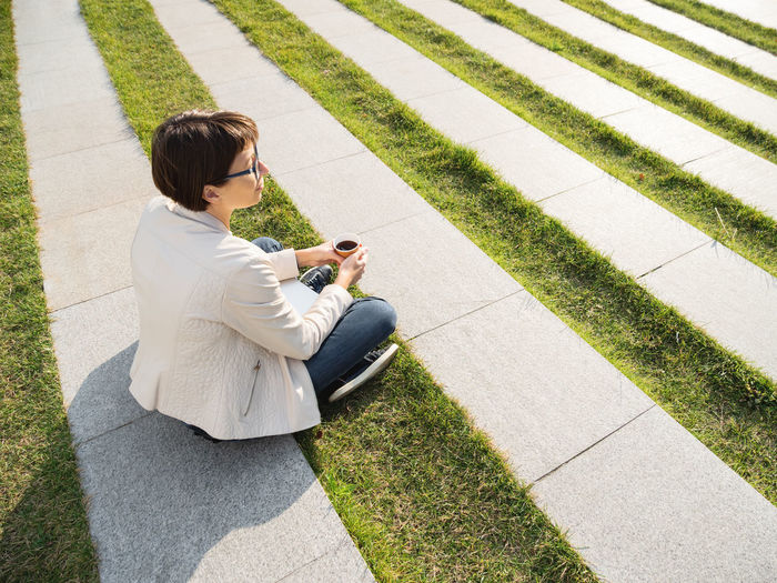 Woman sits in park with take away cup of coffee. casual clothes, urban lifestyle of millennials.