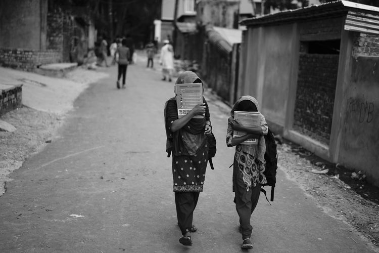 Two girls from the nearby slum, returning home from school. They were actually too shy to be photographed, but I am quite proud that they are continuing school. Hillview H/S, Chittagong. Adult Architecture Building Exterior Built Structure Day Full Length Leisure Activity Lifestyles Men Outdoors People Real People Rear View Togetherness Two People Walking Women