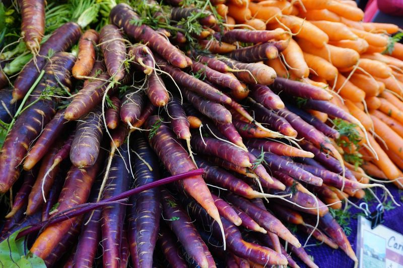 Purple and orange carrots at the farmers market Closeup Community Produce Vegetable Orange Purple Orange Carrot Purple Carrot Farmers Market For Sale Retail  Food Market Food And Drink Healthy Eating Freshness No People Root Vegetable Arrangement Raw Food Carrot