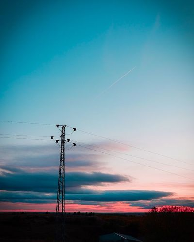 Low angle view of silhouette electricity pylon against sky during sunset