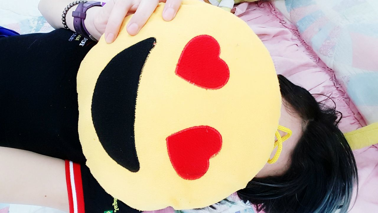 High Angle View Of Woman Holding Smiley Face Cushion While Lying On Bed At Home