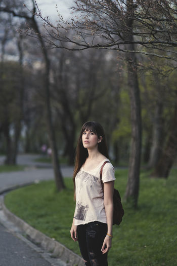 Thoughtful Woman Standing Against Bare Trees At Park