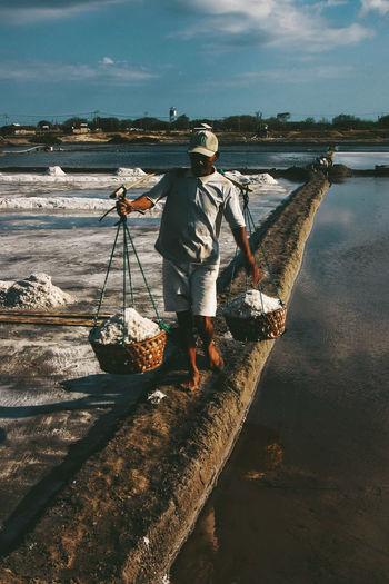 Man carrying salt in baskets