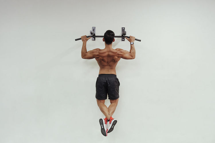 Rear view of shirtless man with arms raised against white background