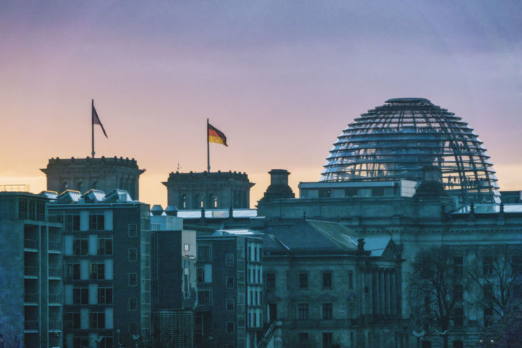 Reichstag And Buildings In City At Sunset