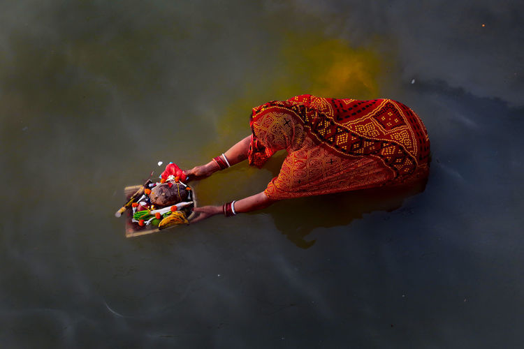 High angle view of woman holding religious offerings in lake
