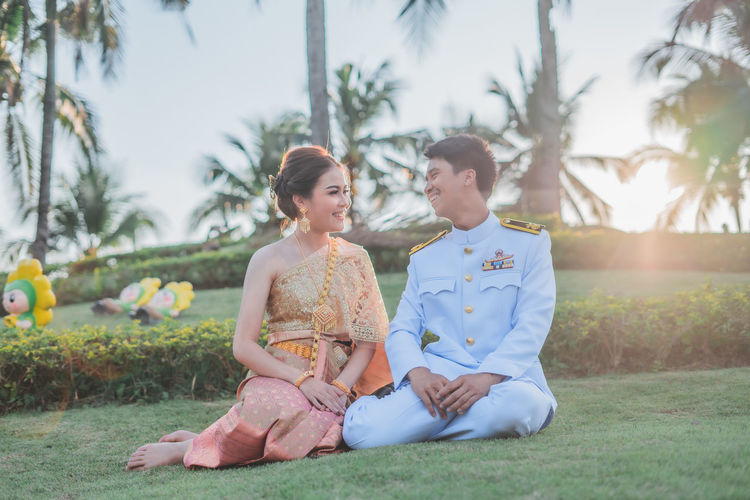 Young couple sitting on land against trees