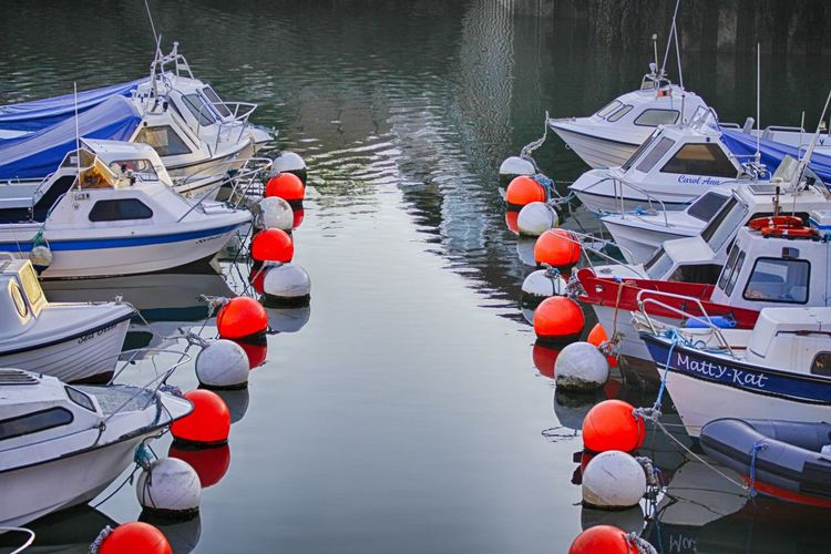 Have you got a light, buoy? Nautical Vessel Moored Water Transportation High Angle View Tranquility Sea Travel Destinations Outdoors Day Buoy Pedal Boat Harbor Vacations No People Nature Boats Marina Buoys Buoy On The Water Symmetry Colors F4 Sommergefühle