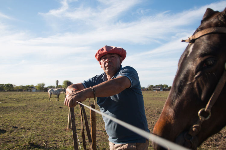 Man posing with his horse in field