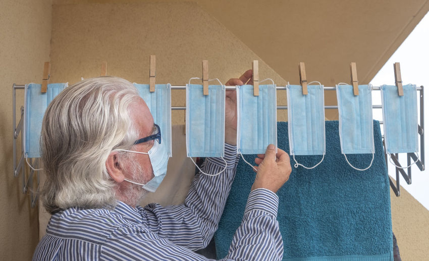 Side view of senior man drying surgical mask on clothesline
